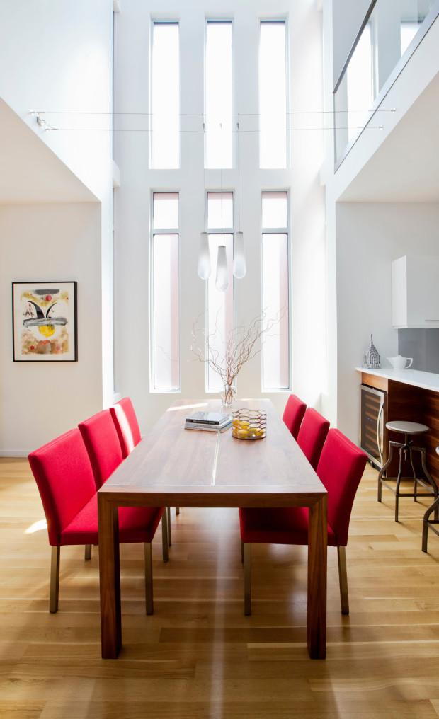 Výška obytného prostoru a dlouhá vertikální okna vnášejí do interiéru záplavu světla. Neutrální barevnost vybavení narušuje jen výrazná červeň jídelních židlí.
