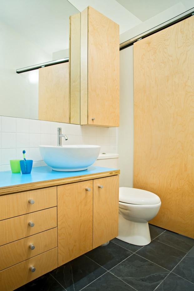 Koupelna je zařízena jednoduše, a to nábytkem vyrobeným na míru z březové překližky. Neutrální barevné spektrum oživuje výrazná modrá deska pod umyvadlem.