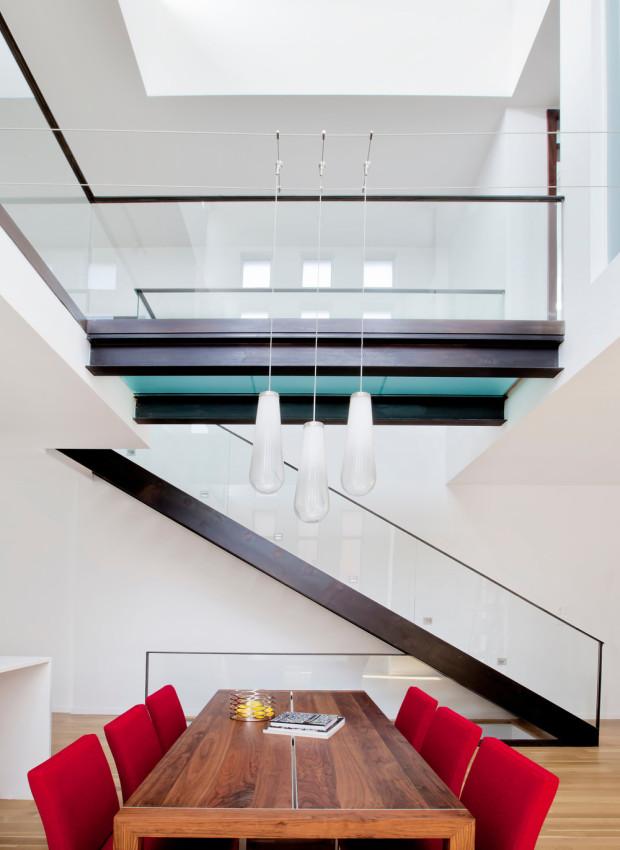 Lávka ve druhém nadzemním podlaží překlenuje otevřený prostor obývací části a spojuje dvě galerie s ložnicemi. Lustr nad jídelním stolem je z důvodu absence stropu zavěšený na ocelových lankách.