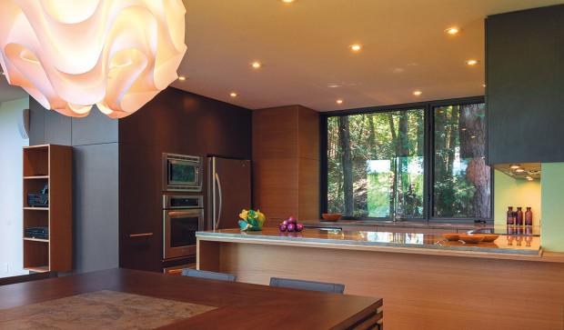 Příroda se promítá dovnitř interiéru nejen prostřednictvím výhledů, ale také zvoleným vybavením. Celá kuchyně je vyvedená ze dřeva.