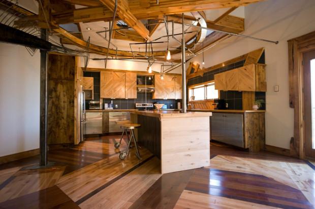 Kuchyně vypadá celkem konvenčně, až na zkosené hrany skříněk, netradiční práci s dřevěným vzhledem a spodní dvířka z perforovaného plechu.