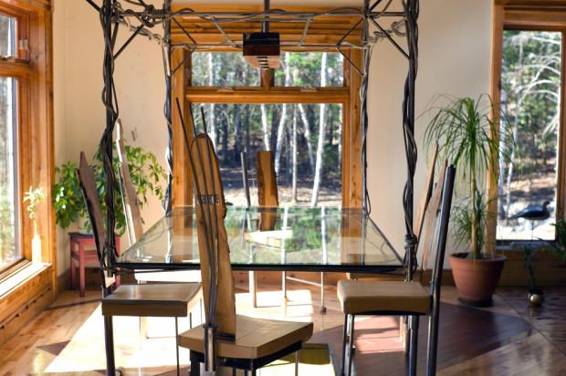 Skleněný jídelní stůl Lachance obrátil vzhůru nohama a jeho kovovou konstrukci zavěsil ze stropu.
