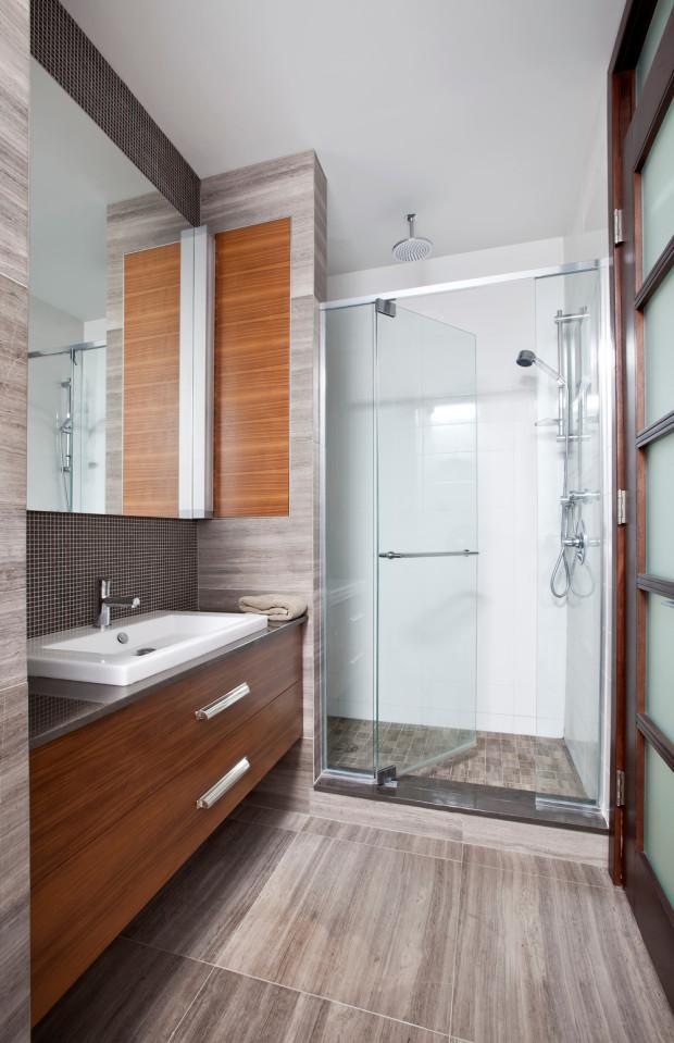 Koupelna souzní s celkovým pojetím domu: jednoduchá, funkční řešení, tlumené přírodní odstíny, praktické a kvalitní materiály (dřevo, kov, sklo).