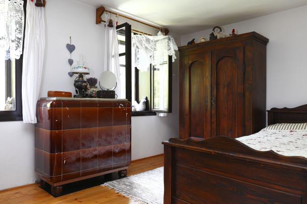 """Nábytek v ložnici v přízemí je vyroben na míru ze starého dřeva – spolu s ním získal požadovanou patinu. Stará elektrická pec je tady zejména na ozdobu. """"Je funkční, ale nikdy jsme ji vlastně nepoužili – nebylo třeba. Systém vytápění pecemi funguje spolehlivě."""""""