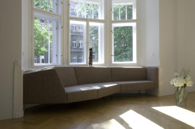Originální sedačka pod oknem jako šedá skulptura doplňuje dřevem obložený výklenek. (foto: Jiří Ernest)