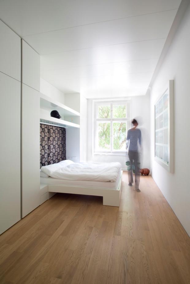 Ložnice je opět v bílé barvě s akcenty v podobě květovaného polstrování za postelí, prostorových objektů a obrazu naproti lůžku.