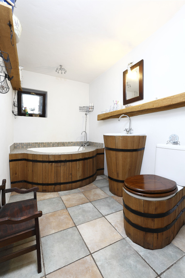 Běžné umyvadlo a WC se změnily na neobyčejné díky dřevěnému obkladu, po vzoru sudu spoutaného ocelovou obručí. Vanu-sprchu vytvarovali na místě a její vnitřek upravili vrstvou vodostálé omítky.