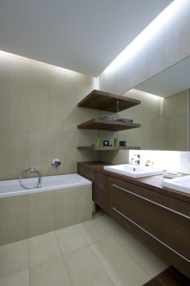 Koupelna v přírodně béžových odstínech s nábytkem z tmavého dřeva.