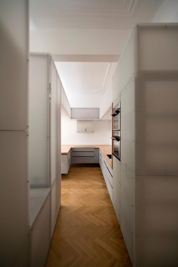 Absolutní jednota. Pohled do kuchyně, která je také tvořena plastovou strukturou. Industriální atmosféru zjemňují právě původní parkety.