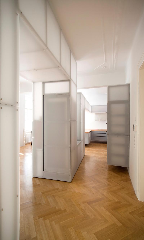 Působivý kontrast nového se starým. Zrenovované parkety, které najdeme ve všech obytných místnostech, sjednocují prostor a vytvářejí pozadí pro moderní, až futuristicky působící strukturu vinoucí se celým bytem.