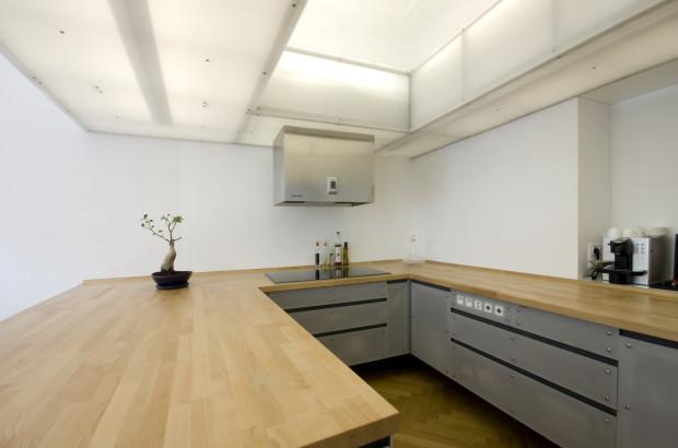 Kuchyň je tvořena spodními skříňkami. Horní část nejsou skříňky, nýbrž struktura naplněná osvětlením a ta se vznáší jako mrak, kterým prostupuje sluneční světlo. Použití materiálu a barevná střídmost vytváří až sakrální dojem. (foto: Jiří Ernest)