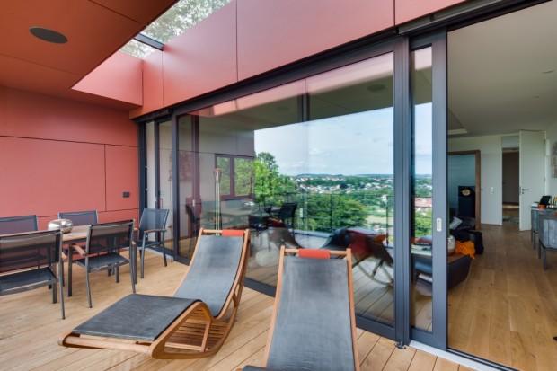 Obývací prostor a terasa v prvním patře. Velké posuvně zdvižné dveře ze systému Schüco ASS 70.HI v šířce 6,44 m a výšce 2,67 m. Prosklená část střechy zajišťuje dostatečný přísun světla.