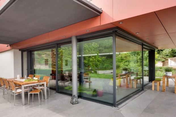 Transparentní prostor kuchyně a kryté terasy v přízemí. Konstrukčně jde o kombinaci posuvného systému Schüco ASS 70.HI s pevnými částmi z fasádního systému Schüco FW 50+.SI.