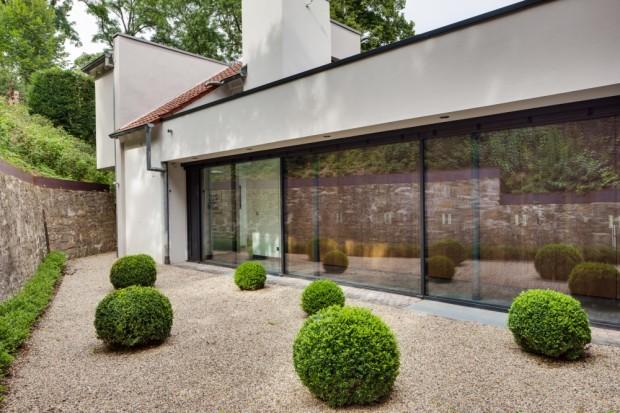 Přechod k původní, v roce 1987 renovované, budově (sousedící zleva). Ta nabízí dalších 120 m2 prostoru pro hosty a rodinu. Plochy s pevným zasklením (Schüco FW 50+.HI v rozměru 10,71 x 2,5 m) i prosklené dveře do objektu vnášejí dostatek denního světla.