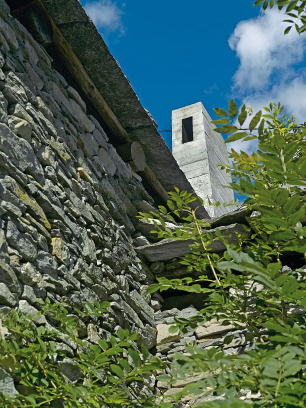 Betonový komín askleněné dveře do zahrady jsou jedinými zvenčí viditelnými důkazy nového života vdvousetleté budově.