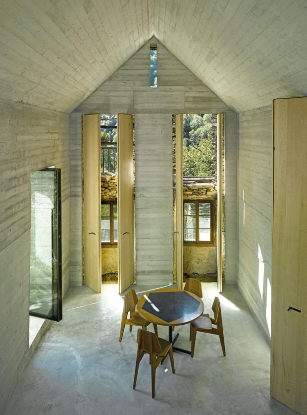 Vysoké úzké otvory vnovýchstěnách korespondují sdveřmi aokny původní stavby. Za dubovými okenicemi se otevírá nejen výhled ven, ale ipohled na původní stěny azachovalá okna adveře. (Pohled zvyvýšeného místa na spaní.)