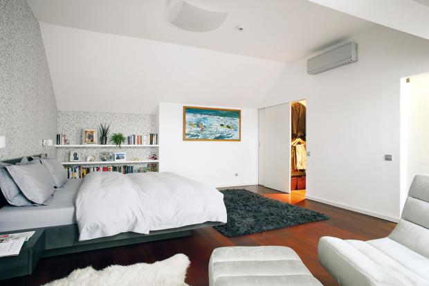 Ložnice manželů. Stěny zdobí dekorační tapeta srostlinným motivem, příjemnou dřevěnou podlahu ještě zútulňují kožešiny akoberec. Foto Robert Žákovič
