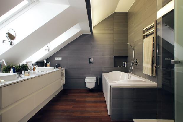"""Šedo-bílou kombinaci na dřevěném """"základu"""" najdeme ivrodičovské koupelně. Poskytuje skutečně královské pohodlí: velkou vanu, sprchový kout idvě umyvadla. Foto Robert Žákovič"""