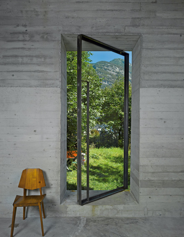 Introvertní budova má jen jedny nové dveře – skleněné vocelovém rámu, které zároveň poskytují výhled na panorama údolí.
