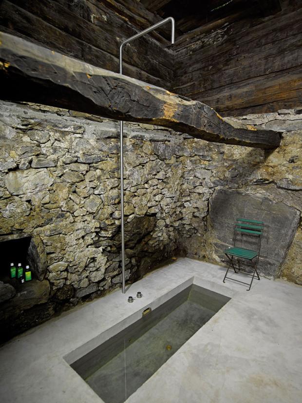 Koupelna se zapuštěnou betonovou vanou má atmosféru prastaré svatyně. Kdysi se tu sušily kaštany.