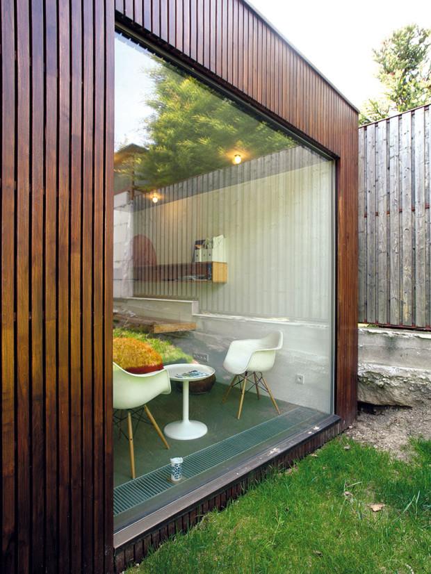 Dřevěný obklad fasády odlišuje přístavbu od původního rodinného domu anavozuje dojem zahradního domku. Přístavba má jednoduchou pravoúhlou formu splochou střechou aje postavena ztradičních materiálů – cihel Porotherm vkombinaci socelobetonovými stropními deskami azaložením na betonové desce.
