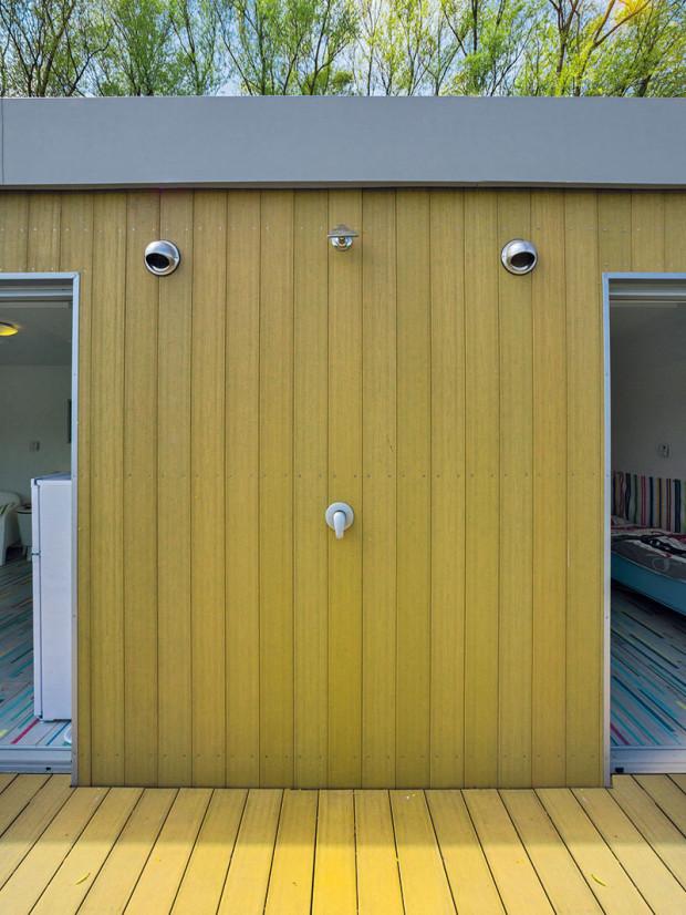 Na fasádě plovoucí chaty se nachází exteriérová sprcha sloužící na opláchnutí po koupání se vřece nebo na osvěžení během horkých dnů.