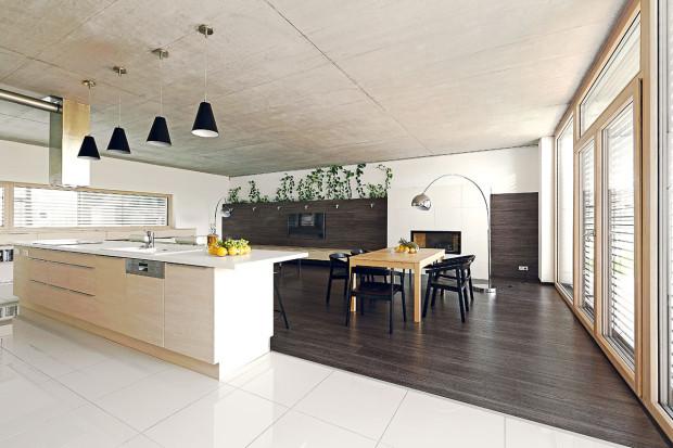 Funkční rozdělení hlavního obytného prostoru zvýrazňuje bílá kuchyňská dlažba kontrastující stmavou laminátovou podlahou vobývacím pokoji.