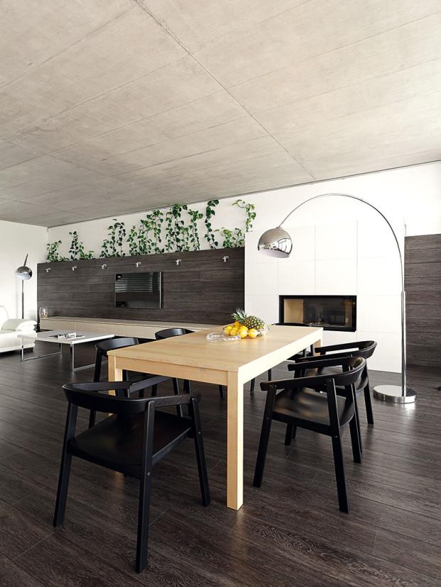 Jídelní stůl pro šest lidí osvětluje stojací lampa, která nevyžaduje zásah do betonového stropu.