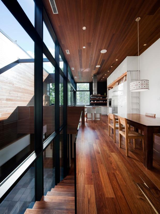 Interiéru dominuje dřevo na podlaze, stropě i nábytku, jehož strukturu akcentují jednolité bílé plochy. Rušivých barevných či vzorových elementů zde najdeme jen minimum.