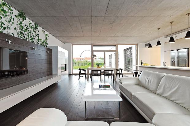 Rýhy vpohledovém betonu na stropě nejsou náhodné. Jsou záměrným prvkem, který dává prostoru řád. Chytré umístění sedací soupravy umožňuje pohled na TV, krb i do zahrady.