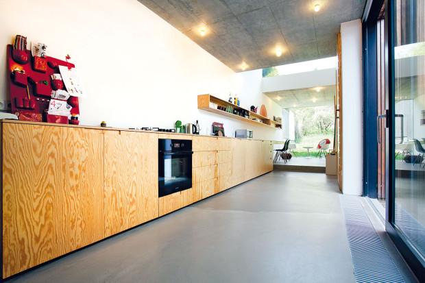 """Kuchyňská linka kontinuálně přechází do pracovního stolu. Docílit zdánlivě přirozeného však nebylo jednoduché: """"Problém byl svýškou – pracovní plocha vkuchyni má mít výšku 90 cm, pracovní stůl 75 cm. Vyřešili jsme to zvednutím podlahy ojeden schůdek,"""" vysvětluje architekt."""