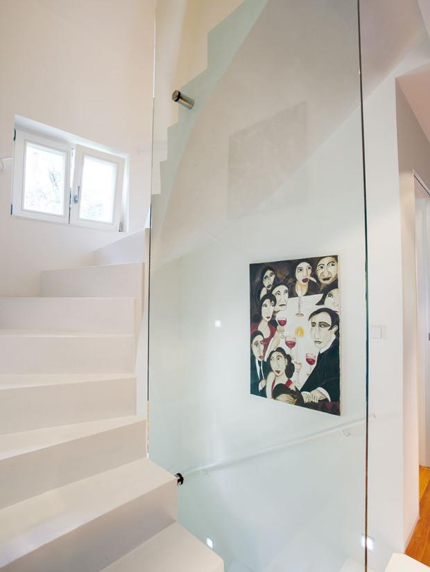 Spirálovitě zatočené schodiště vyráběli ručně dva stavebníci aje chloubou domu. Původně majitelé chtěli, aby dojem zněj nic nerušilo, ale kvůli bezpečnosti dětí bylo nutné přidat zábradlí zvrstveného skla. Sklo naštěstí ubralo odlehčenému dojmu konstrukce jen minimálně.