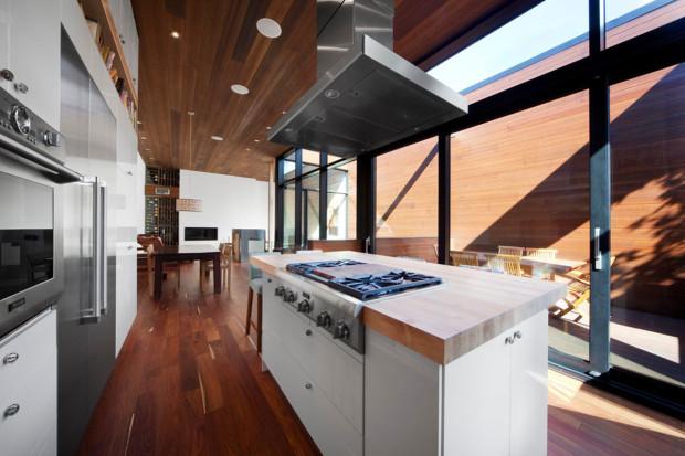 Jednoduché bílé kuchyni s nerezovými akcenty dominuje velký pracovní ostrov s deskou z masivního dřeva. Při práci v kuchyni můžete být v kontaktu nejen s lidmi uvnitř, ale i na terase.