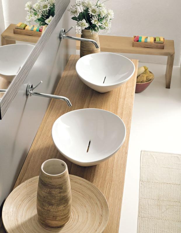 Dřevo vkoupelně. Tvrdé dřeviny dobře snášejí vlhkost ajsou tvarově stabilní, proto jsou ktomuto účelu ideální. Nejznámější je týk, hodí se také dub, sibiřský modřín, ale ijiné druhy. Dřevo do koupelny se povrchově upravuje − transparentním polyuretanovým lakem či oleji, které dokážou zachovat přirozený vzhled acharakter dřeva. FOTO PERFECTO DESIGN