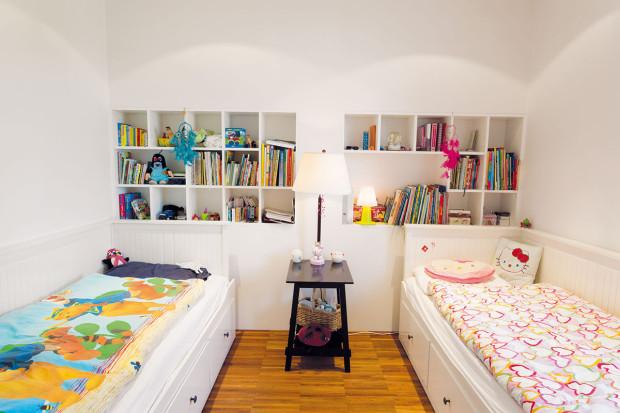 Dětská ložnice je vybavena jednoduše avkusně běžným sektorovým nábytkem. Děti si trochu neobvykle vybraly, že − ač mají kdispozici dva pokoje − budou bydlet spolu. Druhý pokoj jim proto slouží jako prostorná pracovna aherna.