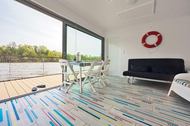 Vplovoucí chatě moc nábytku nenajdete – jen to nejnutnější, majitelům itak nabízí komfort. Bílá barva, proužky azáchranný kruh nad pohovkou dávají prostoru námořnický charakter.
