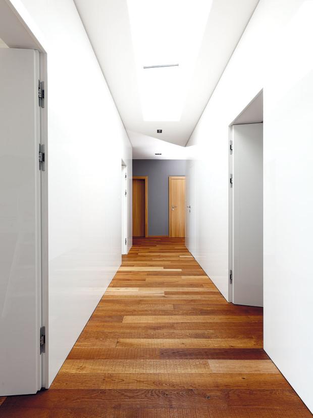 """Vchodbě vnoční části domu je šestero dveří, což byla pro architekta zajímavá výzva: """"Nechtěl jsem, aby to vypadalo jako vhotelu: dveře, zárubně, kousek omítky, zárubně, dveře… Navrhli jsme proto velmi čisté řešení, kde nejsou vidět zárubně adveře lícují se stěnou. Naštěstí už déle spolupracujeme sfirmou, která dokáže realizovat ityto náročné detaily."""""""