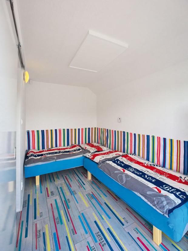 Ložnice jsou vplovoucí chatě dvě – jedna slouží rodičům, druhá dětem. Pro oživení ipohodlné opření je vté dětské za postelemi umístěn pruhovaný látkový sokl vživých barvách.