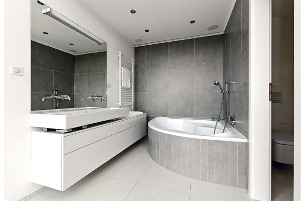 Rohová vana byla požadavkem majitelů. Architekti tuto výzvu přijali aobložením sladili vanu se zbytkem interiéru.