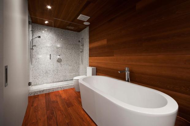 Koupelna ponechává plné pole působnosti přirozené struktuře dřeva, které vyniká v kombinaci s jednoduchou bílou sanitou. Strakatý mozaikový obklad sprchového koutu je opět jen decentním poškádlením jinak čistého vzhledu.