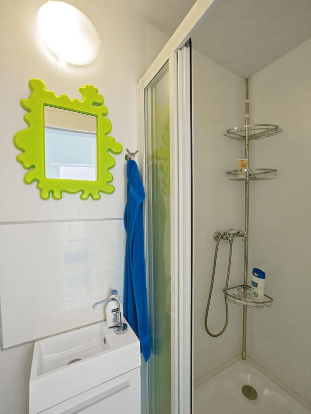Koupelna stoaletou je malá, ale funkční. Vanu vestísněnějších podmínkách nahradil sprchový kout. Bílá barva prostor opticky zvětšuje, svěžím akcentem je zrcadlo se zeleným rámem.