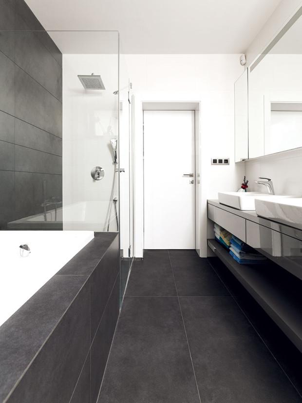 Barevná kombinace šedé abílé, sněkolika černými detaily adřevem, je základem všech interiérů, koupelny nevyjímaje. Takový evergreen.