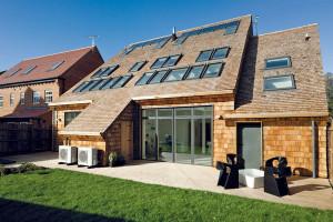 Stavba má téměř tradiční vzhled – fasáda sobkladem zdřevěných šablon připomíná vAnglii oblíbené neomítané zdivo, šikmá střecha ladí sokolní zástavbou.