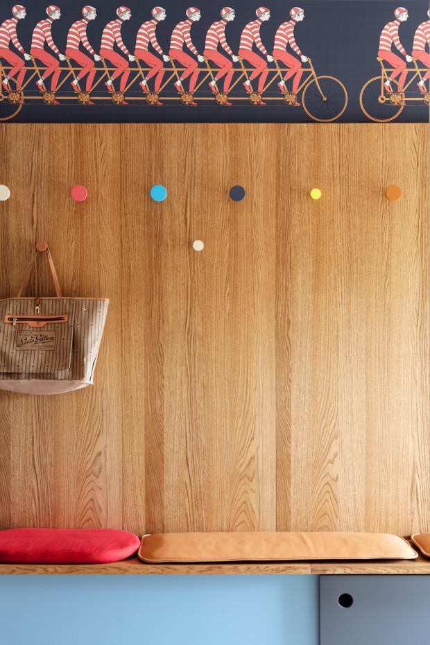 Dřevěnou stěnu oživují barevné kulaté věšáky na zavěšení oděvů a také veselý motiv cyklistů.