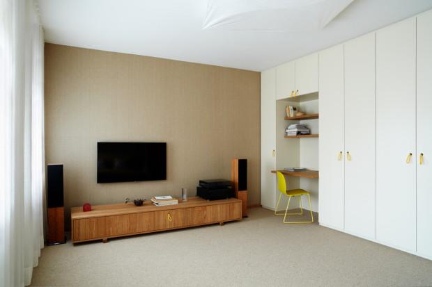 V celém interiéru se vyskytují výrazné barevné solitéry, které vytváří jakousi mozaiku dekorativních prvků v retro designu. Zde je takovým barevným akcentem žlutá židle u pracovního koutu a červené hodiny. Nad celým prostorem se vznáší bílé svítidlo Ariette od Flos.