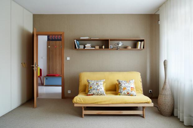 Stojací lampa Bolla od Gervasoni, z přírodního ratanu, zajímavě osvětlí stěny pokoje a promítne tak na ně svůj vzor. Podlahu pokrývá béžový koberec Signature Berber od Bewe z vlny.