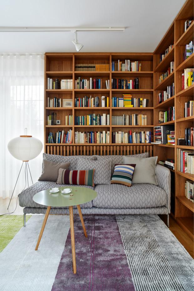Dubová knihovna s rohovou sedačkou Moroso − celek doplňuje servírovací stolek, podle návrhu architekta (v bruselském stylu) a stojací svítidlo od Vitry.