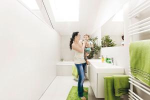 Také vkoupelnách vládne minimalismus. Pro dům typická bílá barva je oživena, jak jinak, svěžími zelenými doplňky. Nechybí dvojité umyvadlo nabízející větší komfort zejména během hektičtějších rán.