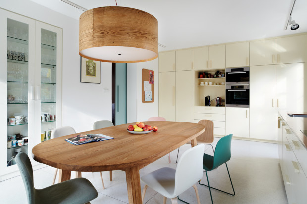 Dubový stůl obklopují stylové dánské jídelní židle Muuto (dodalo Scandium). Struktura dřeva je rovněž motivem centrálního svítidla, jehož stínítko je vyrobeno z dýhy.