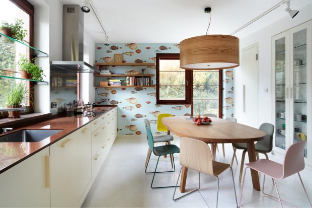 Tapeta Cole&Son Fornasetti Acquario pokrývá jednu stěnu, v místnosti funguje jako obraz s hravým motivem. Na stěně s tapetou je knihovnička pro kuchařky, které jsou tak pohodlně při ruce.